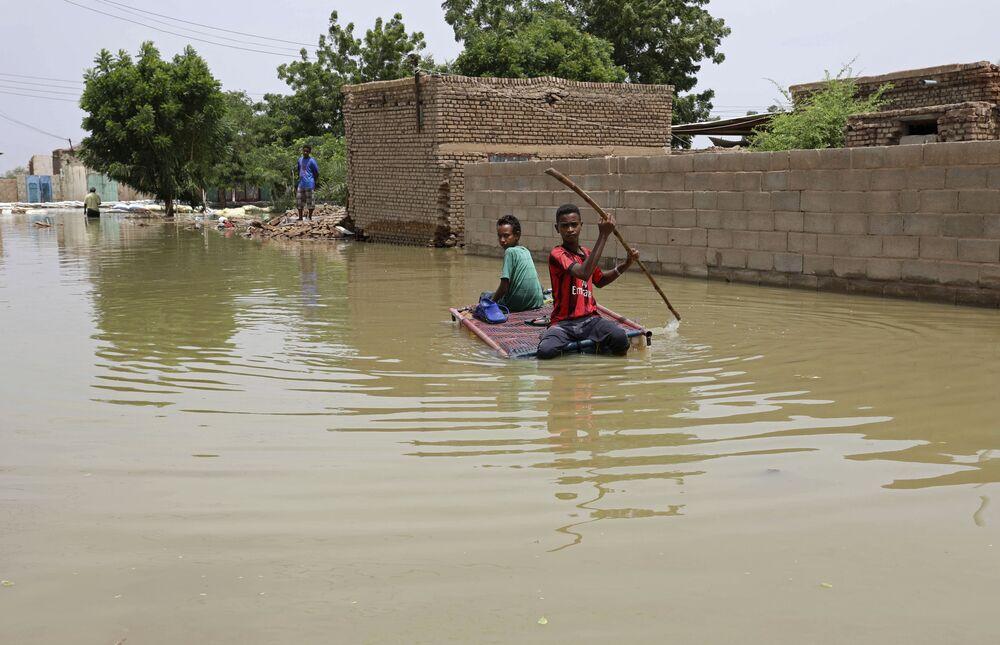 Nastolatkowie pływają na tratwie po zalanej ulicy w Salmaniya w Sudanie