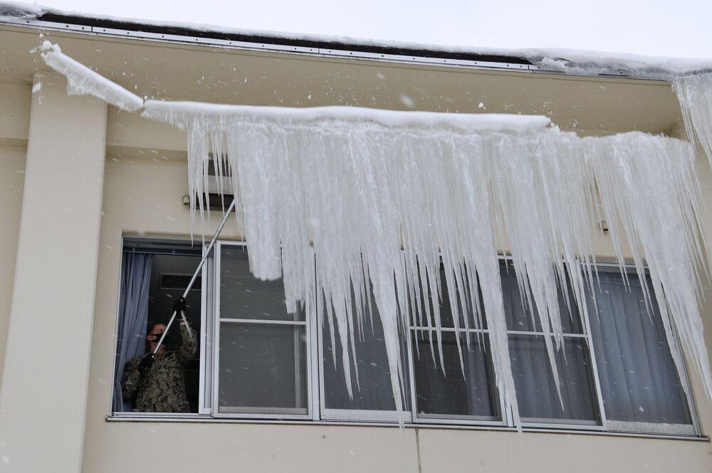 Amerykański żołnierz z bazy Misawa usuwa naledź z dachu po silnych opadach śniegu w Japonii.