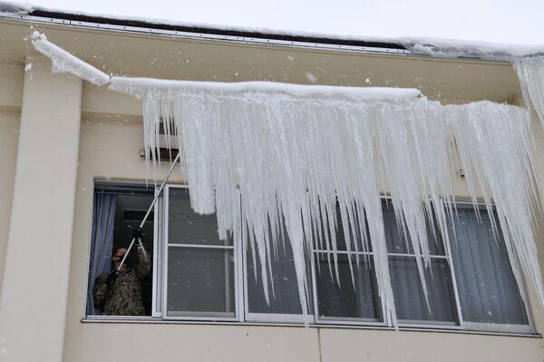Amerykański żołnierz z bazy Misawa usuwa naledź z dachu po silnych opadach śniegu w Japonii - Sputnik Polska