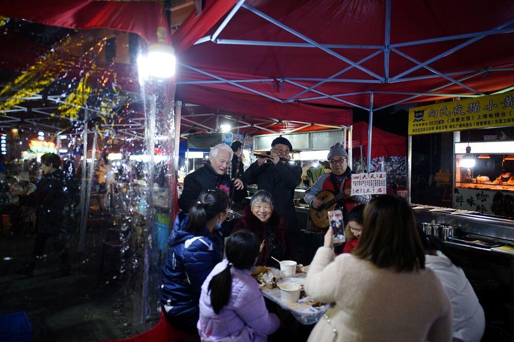 Klienci nocnej restauracji ulicznej w Wuhan.