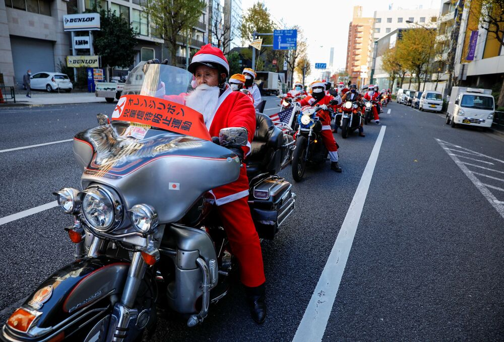 Ludzie przebrani za Świętego Mikołaja jeżdżą na motocyklach Harley Davidson podczas bożonarodzeniowej parady w Tokio