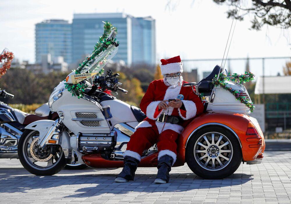 Mężczyzna przebrany za Świętego Mikołaja na motocyklu Harley Davidson podczas bożonarodzeniowej parady w Tokio