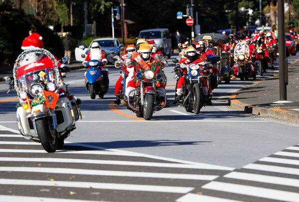 Ludzie przebrani za Świętego Mikołaja jeżdżą na motocyklach Harley Davidson podczas bożonarodzeniowej parady w Tokio - Sputnik Polska