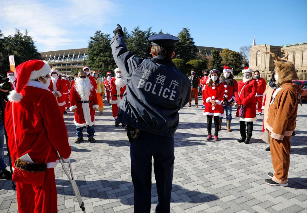 Policjant z uczestnikami przebranymi za Świętego Mikołaja podczas parady bożonarodzeniowej w Tokio