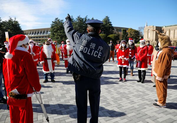 Policjant z uczestnikami przebranymi za Świętego Mikołaja podczas parady bożonarodzeniowej w Tokio - Sputnik Polska