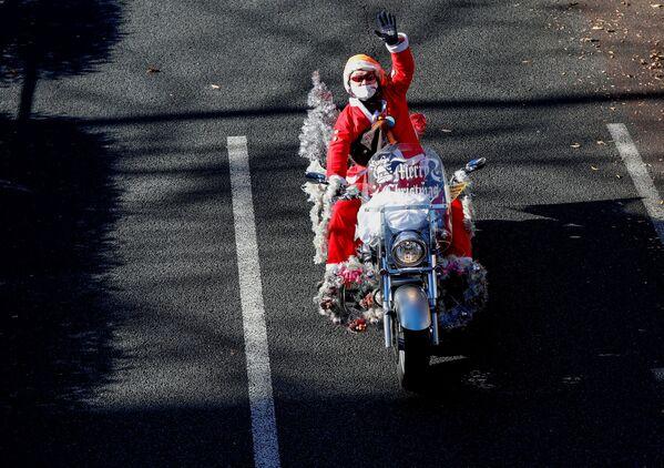 Mężczyzna przebrany za Świętego Mikołaja jedzie na motocyklu Harley Davidson podczas bożonarodzeniowej parady w Tokio - Sputnik Polska