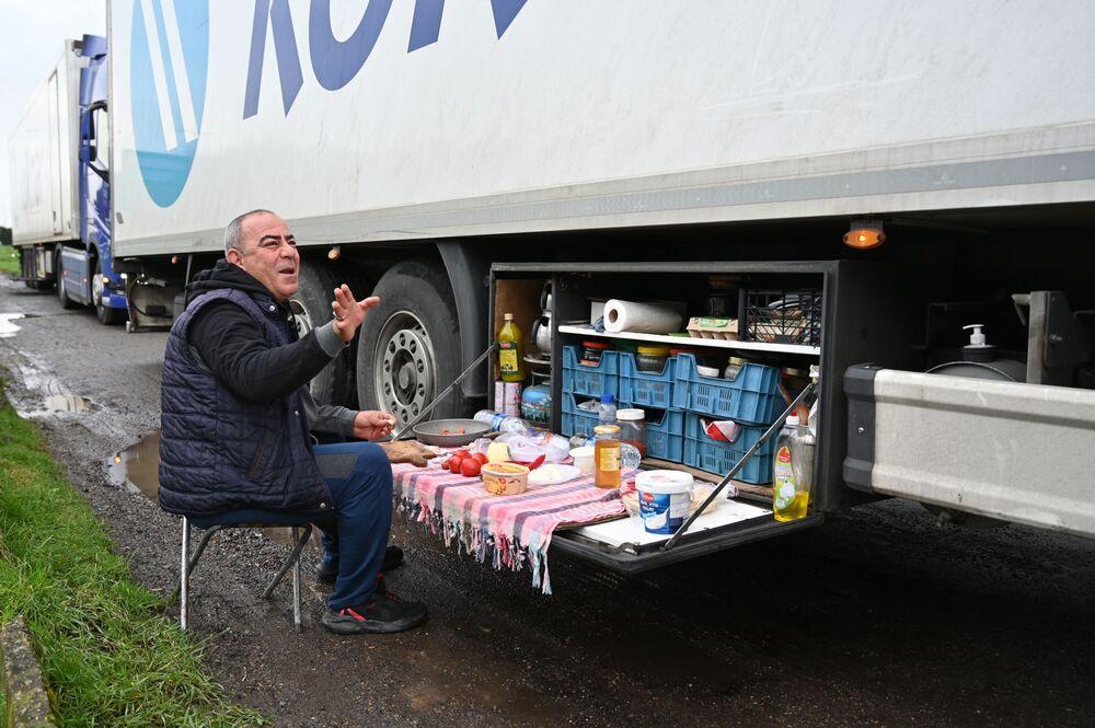 Turecki kierowca ciężarówki je śniadanie na parkingu dla ciężarówek przy autostradzie M20 w południowo-wschodniej Anglii