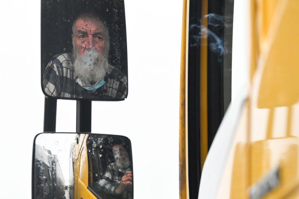 Węgierski kierowca ciężarówki pali, czekając na międzynarodowym parkingu dla ciężarówek w Ashford