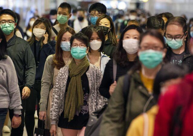 Pasażerowie w maskach medycznych na przejściu metra w Hongkongu.