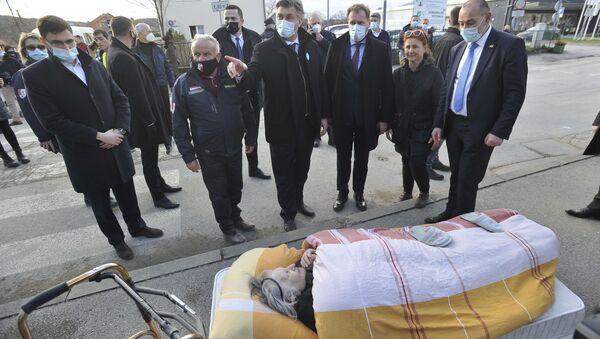 Chorwacki Premier Andrej Plenković obok starszej kobiety ewakuowanej z powodu trzęsienia ziemi w Petrigny - Sputnik Polska