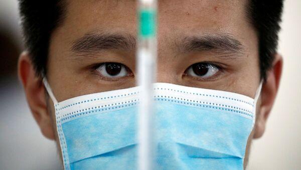 Mężczyzna w masce medycznej w laboratorium chińskiego producenta szczepionek Sinovac Biotech - Sputnik Polska