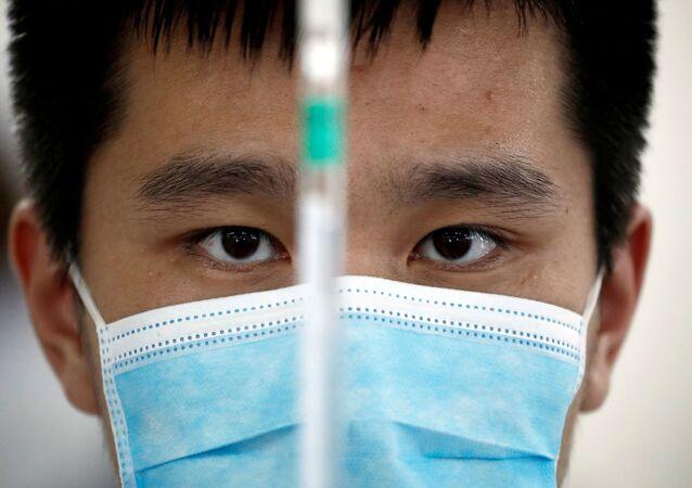 Mężczyzna w masce medycznej w laboratorium chińskiego producenta szczepionek Sinovac Biotech