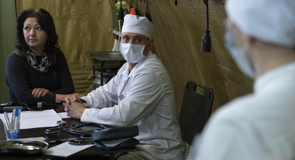 Lekarz przyjmuje pacjenta w szpitalu polowym rozmieszczonym przez rosyjskie Ministerstwo Obrony na lotnisku w Stepanakercie