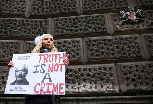 Zwolenniczka założyciela WikiLeaks, Juliana Assange'a, trzyma plakat wspierający go przed Central Court w Londynie - Sputnik Polska
