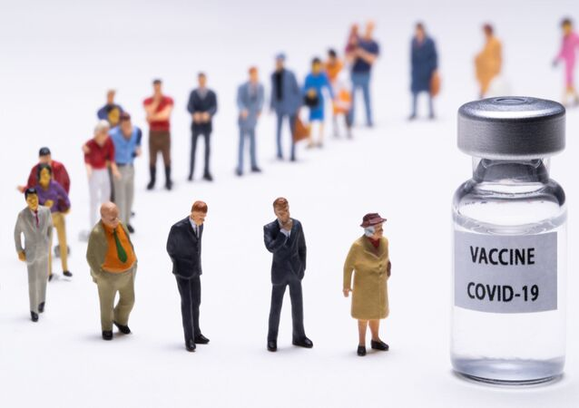 Figurki obok fiolki ze szczepionką