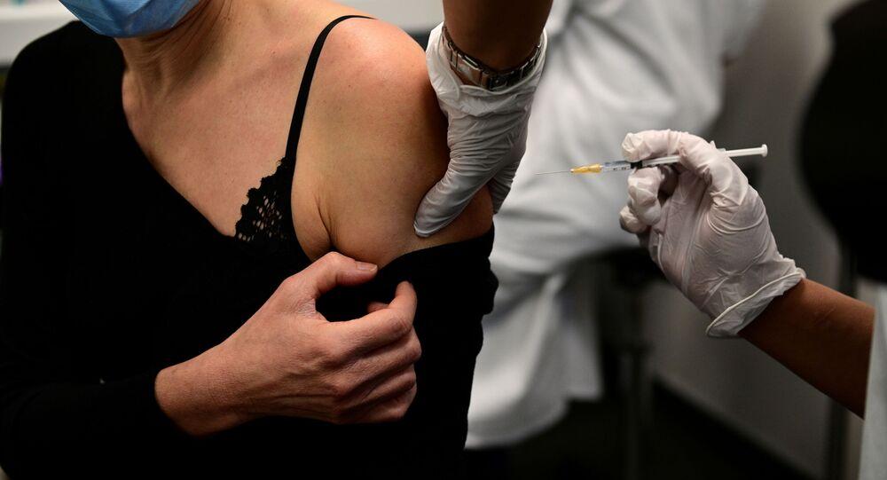Kobieta otrzymuje szczepionkę podczas kampanii szczepień pracowników służby zdrowia w wieku powyżej 50 lat lub z chorobami współistniejącymi w centrum szczepień w hotelu Dieu (Assistance Publique - Hopitaux de Paris) w Paryżu, Francja, 4 stycznia 2021 r.