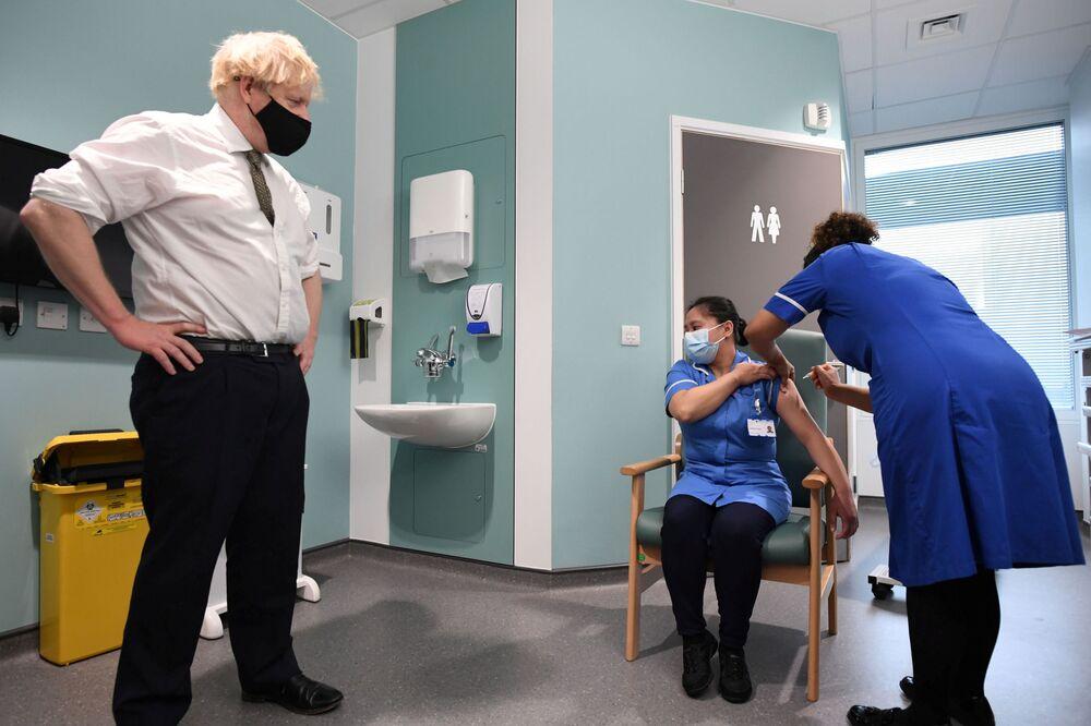 Boris Johnson przygląda się, jak Jennifer Dumasi otrzymuje szczepionkę przeciwko COVID-19 podczas swojej wizyty w szpitalu Chase Farm w północnym Londynie w Wielkiej Brytanii 4 stycznia 2021 r.