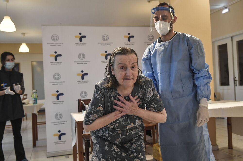 Kobieta okazuje wdzięczność po zaszczepieniu się przeciwko COVID-19 w domu opieki na północnych przedmieściach Aten 4 stycznia 2021 r.