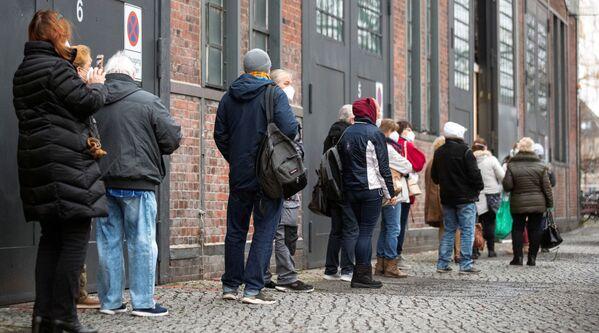 Ludzie stoją w kolejce do ośrodka szczepień przeciwko koronawirusowi w Berlinie, 4 stycznia 2021 r. - Sputnik Polska