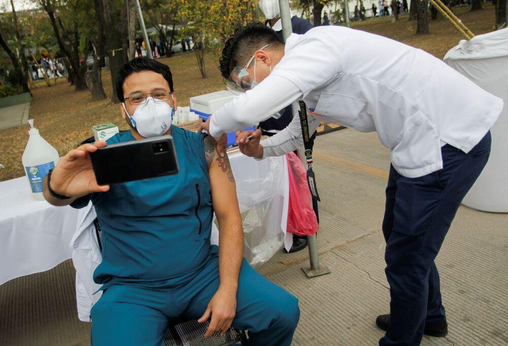 Pracownik medyczny robi selfie, gdy otrzymuje zastrzyk z dawką szczepionki Pfizer-BioNTech COVID-19 w Regionalnym Wojskowym Szpitalu Specjalistycznym w San Nicolas de los Garza, na obrzeżach Monterrey w Meksyku, 29 grudnia 2020 r.