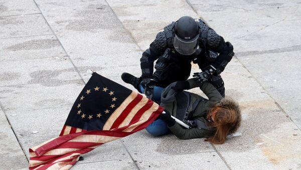Policjant zatrzymuje protestującego przed Kapitolem w Waszyngtonie - Sputnik Polska