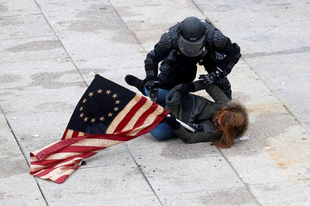 Policjant zatrzymuje protestującego przed Kapitolem w Waszyngtonie