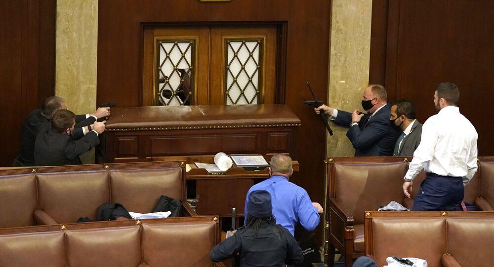 Policjanci celują w drzwi, gdy demonstranci zajmują budynek Kapitolu