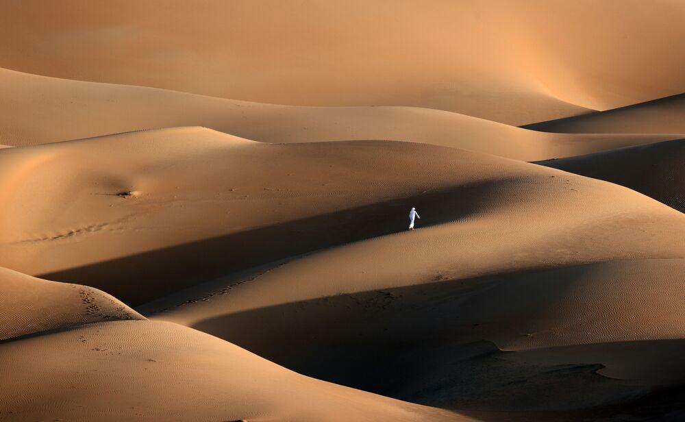 Mężczyzna idący po pustyni Liwa w Zjednoczonych Emiratach Arabskich