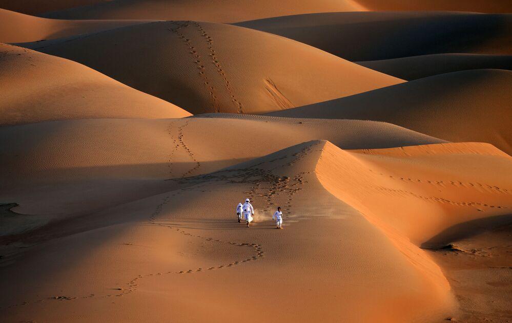 Młodzież biegnie po wydmach pustyni Liwa w Zjednoczonych Emiratach Arabskich