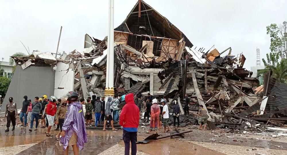 Ludzie patrzą na zniszczony przez trzęsienie ziemi dom na Sulawesi w Indonezji.