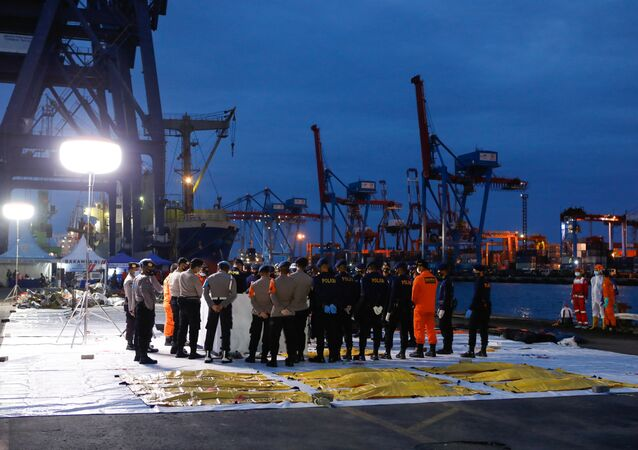 Indonezyjscy policjanci badają szczątki z rozbitego samolotu Sriwijaya Air.