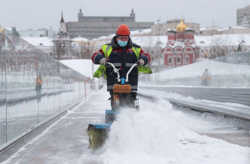 """Pracownik Państwowej Instytucji """"Gormost"""" czyści śnieg i lód na moście w parku"""