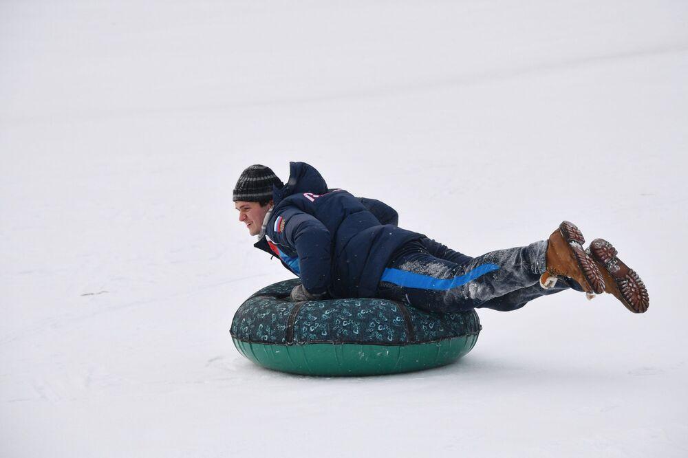 Mężczyzna zjeżdża z górki w parku Kolomienskoje w Moskwie