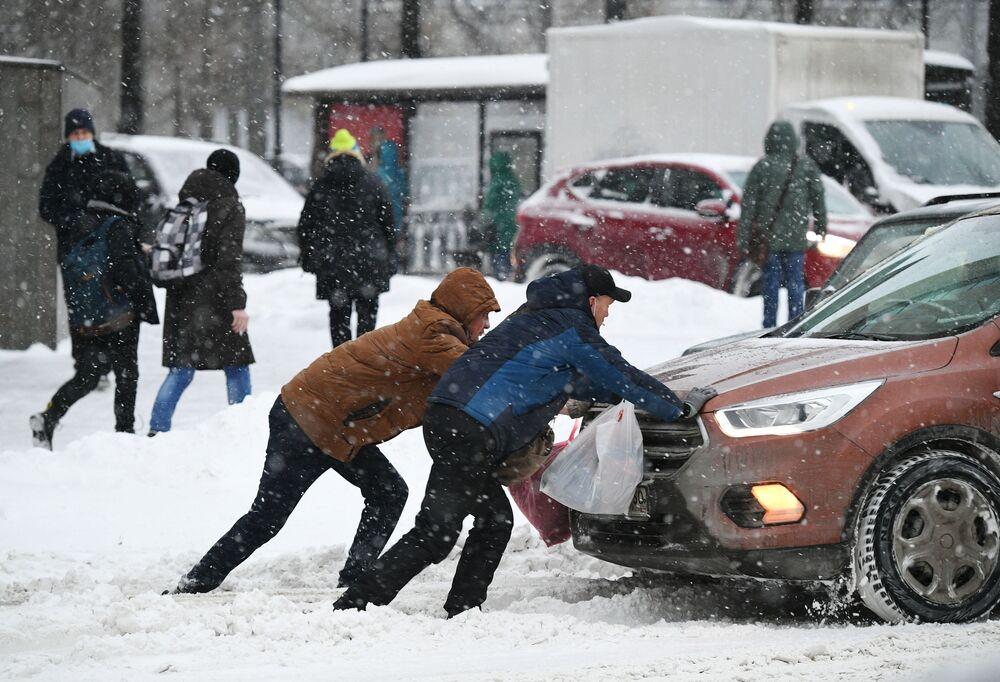 Mężczyźni pchający samochód, który utknął na jezdni podczas opadów śniegu
