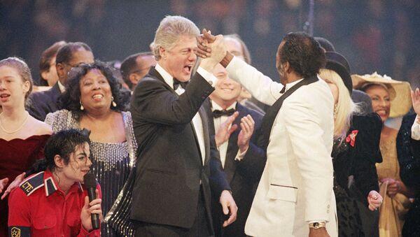 Prezydent elekt Bill Clinton przybija piątkę Chuckowi Berry'emu podczas finału Gali Prezydenckiej w Capital Center w Landover,  19 stycznia 1993 roku. Po lewej stronie Michael Jackson i Chelsea Clinton - Sputnik Polska