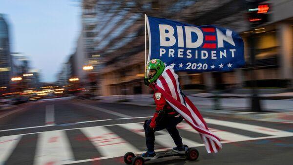 Zwolennik prezydenta elekta Joe Bidena jedzie na deskorolce przed Białym Domem w dzień inauguracji Bidena w Waszyngtonie  - Sputnik Polska