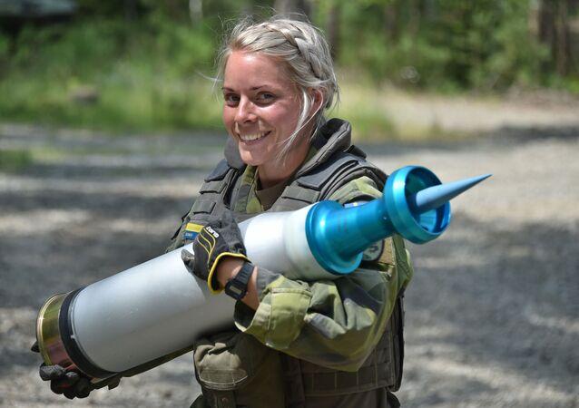 Żołnierka szwedzkiej armii nosi pocisk podczas testów czołgów Strong Europe