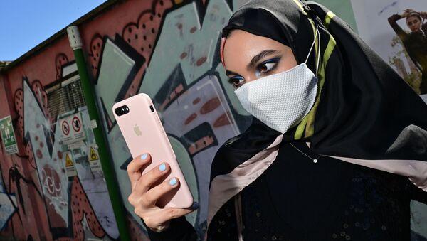 Kobieta w masce z iPhonem w Mediolanie we Włoszech - Sputnik Polska