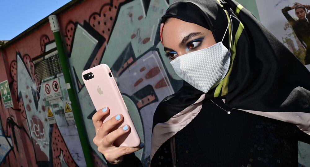 Kobieta w masce z iPhonem w Mediolanie we Włoszech