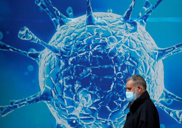 Mężczyzna w masce na tle ilustracji z koronawirusem