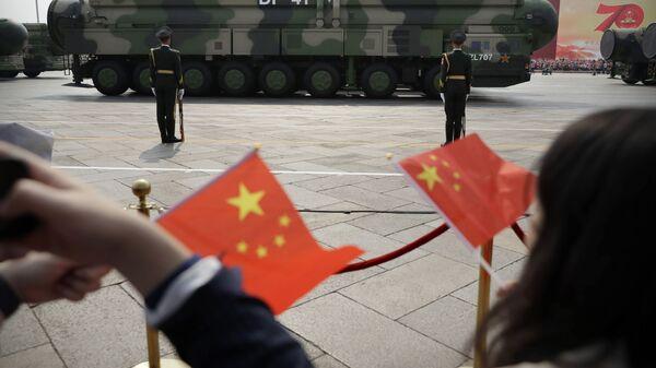 Widzowie na paradzie z okazji 70. rocznicy powstania komunistycznych Chin na tle machiny wojennej z pociskami balistycznymi DF-41 - Sputnik Polska