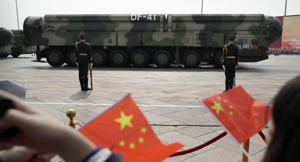 Widzowie na paradzie z okazji 70. rocznicy powstania komunistycznych Chin na tle machiny wojennej z pociskami balistycznymi DF-41