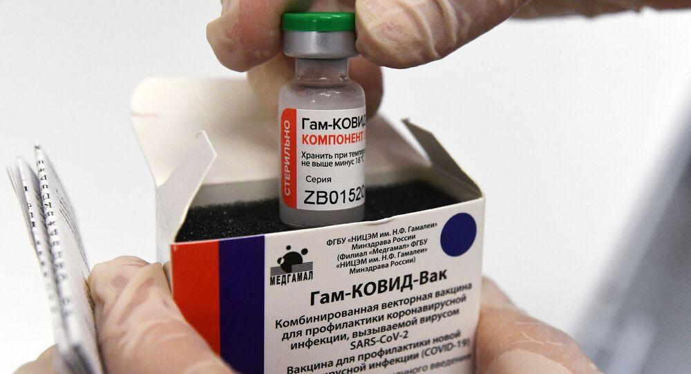 """Pielęgniarka wyciąga ampułkę ze szczepionką przeciwko COVID-19 """"Sputnik V"""" (""""Gam-COVID-Vac"""") w celu zaszczepienia"""