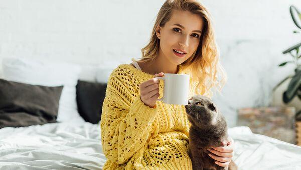 Dziewczyna z kubkiem kawy i kotem - Sputnik Polska