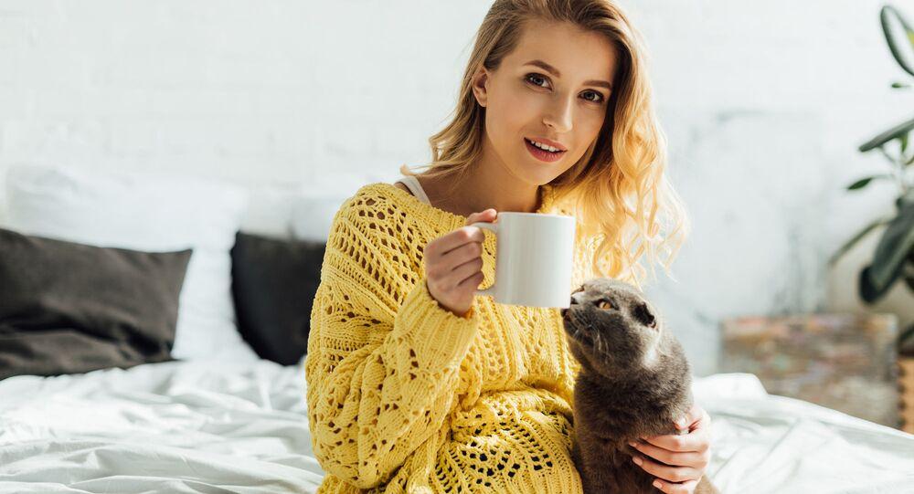 Dziewczyna z kubkiem kawy i kotem