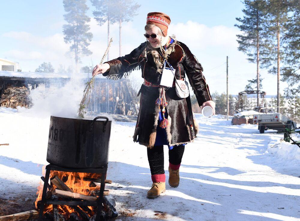 """Praktykujący szaman i strażniczka tradycyjnej wiedzy Samów Nadia Fenina gotuje zupę rybną na festiwalu """"Mistyczna Północ"""""""