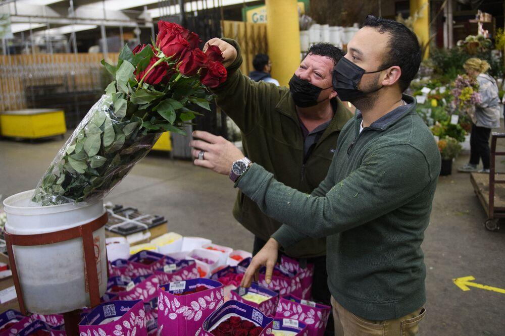 Sprzedawca pomaga klientowi wybrać bukiet kwiatów z okazji Walentynek, Kalifornia