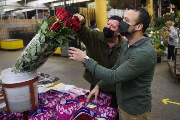 Sprzedawca pomaga klientowi wybrać bukiet kwiatów z okazji Walentynek, Kalifornia  - Sputnik Polska