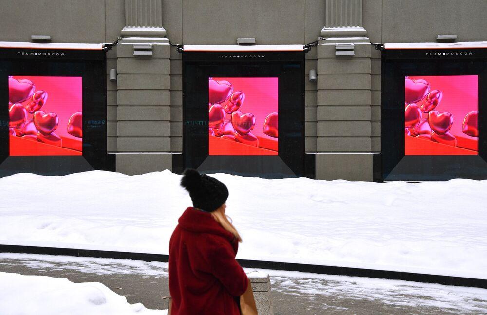 Dziewczyna przechodzi obok galerii handlowej w Moskwie w przeddzień Walentynek