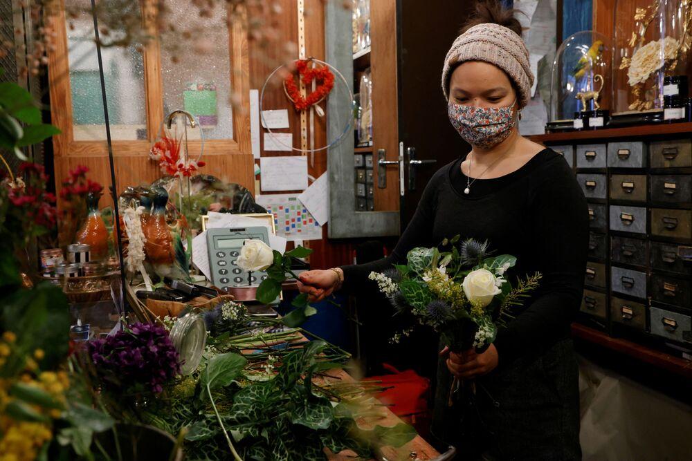 Florystka układa bukiet kwiatów w sklepie w Paryżu
